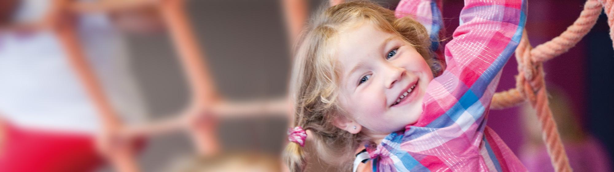 Ein Mädchen klettert an einem Seilnetz und schaut dabei lachend in die Kamera