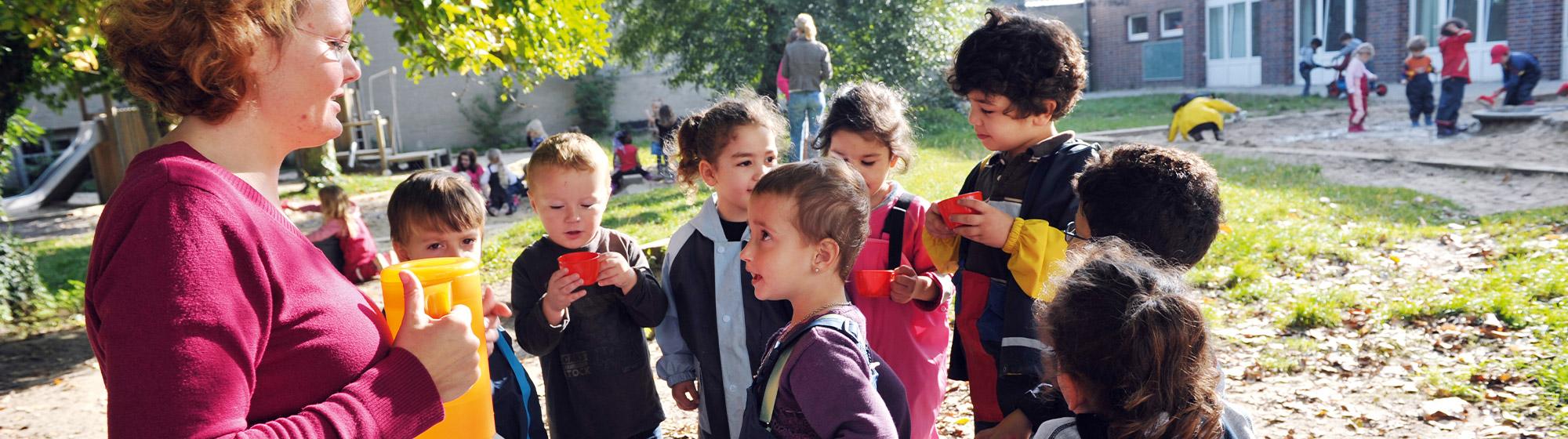 Kindergarten-Außengelände: Es ist gutes Wetter, die Sonne scheint. Im Vordergrund ist eine Erzieherin im Profil zu sehen, die eine Karaffe in der Hand hält. Um sie herum haben sich Kinder mit ihren Getränkebechern versammelt. Im Hintergrund sind weitere spielende Kinder und Erzieher:innen zu sehen.