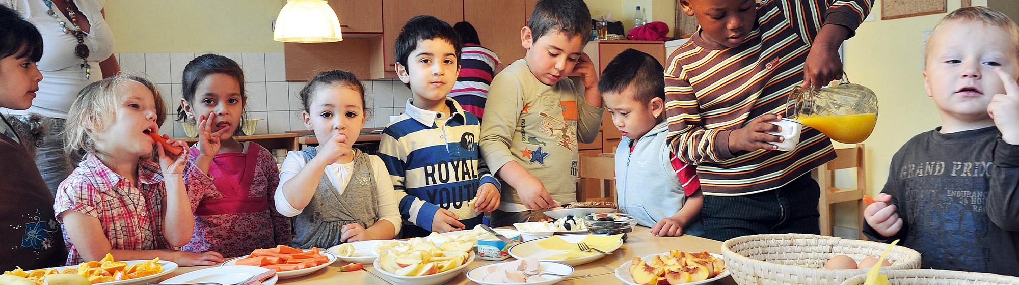 Kindergartenkinder stehen hinter einem Tisch, der mit gesunden Lebensmitteln wie Obst und Gemüse, Käse und Wurst eingedeckt ist. Ein Kind schenkt sich aus einer Karaffe Orangensaft in ein Glas ein. Einige der Kinder schlecken sich genüsslich die Finger ab. Im Hintergrund ist die Küche des Kindergartens zu sehen.