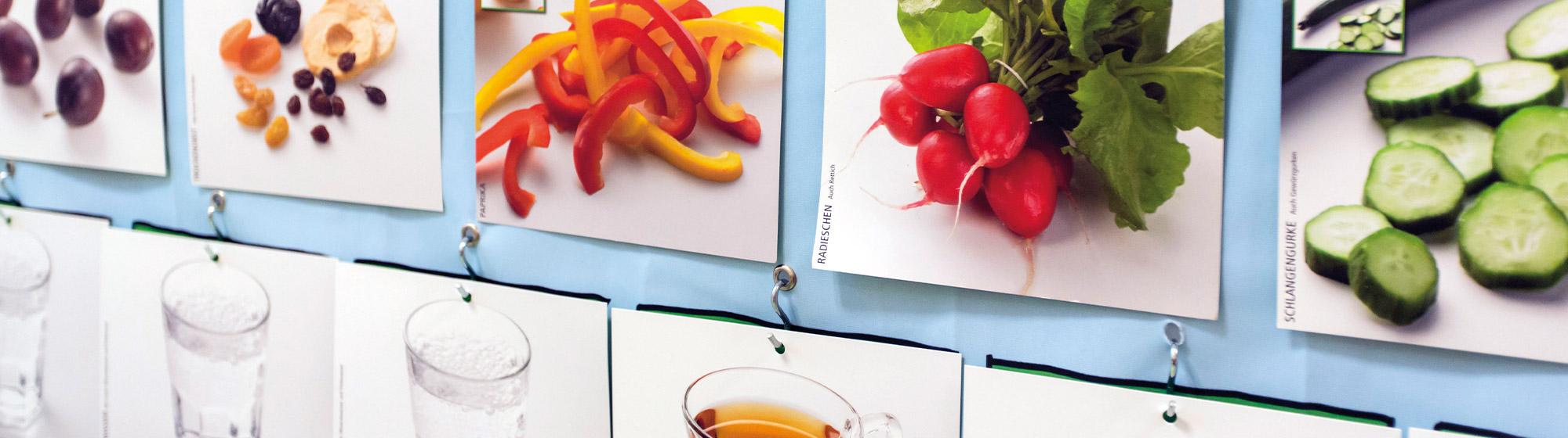 Plakatwand auf der Fotografien von Lebensmittel angepinnt sind: zum Beispiel Backwaren, Kartoffeln, Paprika, Radieschen, Gurken und Getränke wie Wasser und Tee