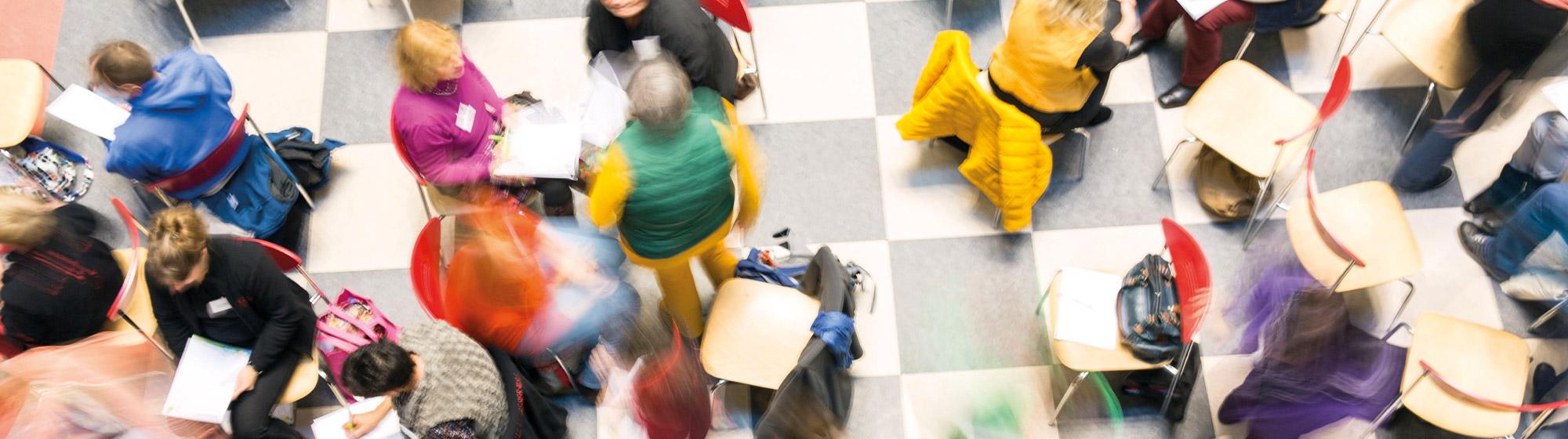 Das Bild ist auf einer ABmPE-Netzwerktagung entstanden. Es zeigt Menschen, die in Gruppen, auf bunten Stühlen, sitzen. Das Bild ist von oben herab fotografiert. Bewegungsunschärfe verzerrt das Bild optisch.